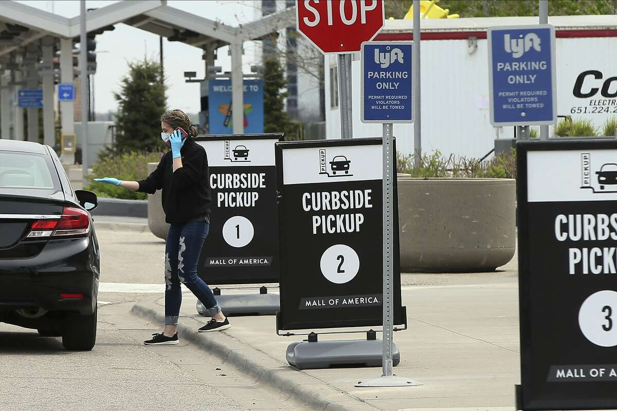 A shopper in a car is assisted at a curbside pickup spot at the Mall of America where shoppers can pick up their orders after buying online or by phone from some mall stores Tuesday, May 5, 2020, in Bloomington, Minn. (AP Photo/Jim Mone)