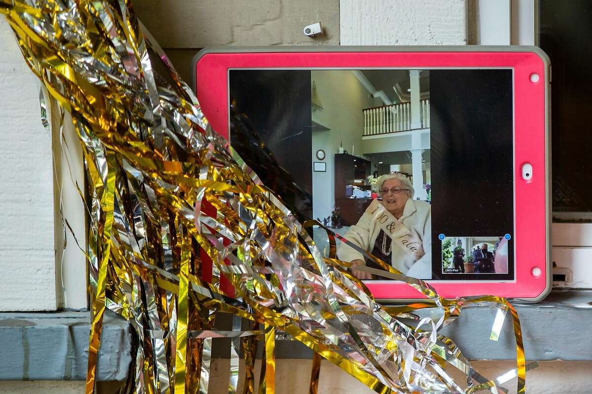 Rhoda Marie Kay chats with her friends and family outside her home through FaceTime on Saturday, May 9, 2020, in South San Francisco, Calif. Kay turned 100 years old. She was celebrated by her family and friends at Aegis Living, the assisted living facility where she resides. Amid the coronavirus pandemic, she did not leave the facility and saw her friends and family through a window.
