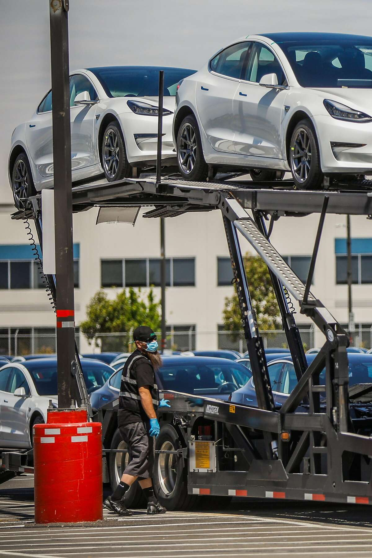 A man loads cars at the Tesla car factory on Monday, May 11, 2020 in Fremont, California. Tesla has reopened its Fremont car factory in defiance of county rules prohibiting car manufacturing during shelter-in-place.