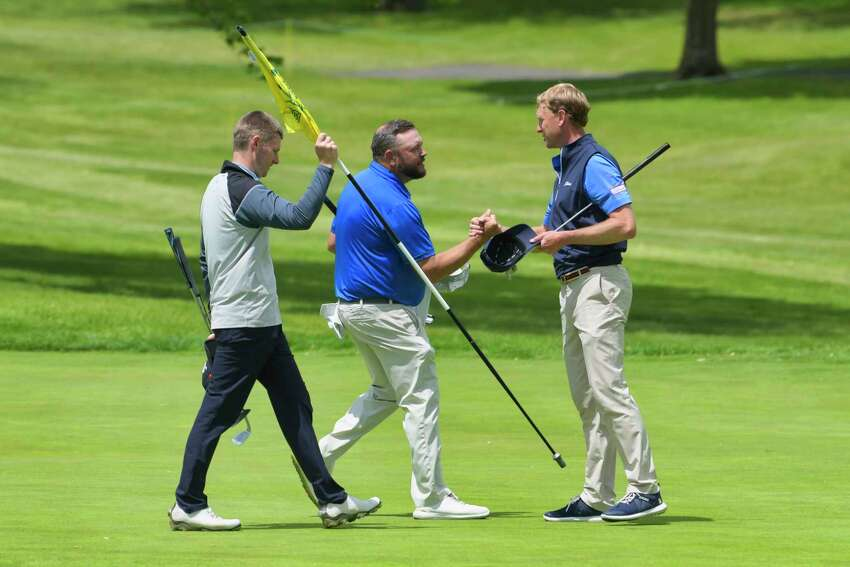 Chris Sanger, left, Scott Berliner, center, and Anders Mattson, shake hands on the 18th green as they finish the final round of the Northeastern New York PGA Stroke Play Championship at Wolferts Roost Country Club on Wednesday, May 22, 2019, in Albany, N.Y. (Paul Buckowski/Times Union)