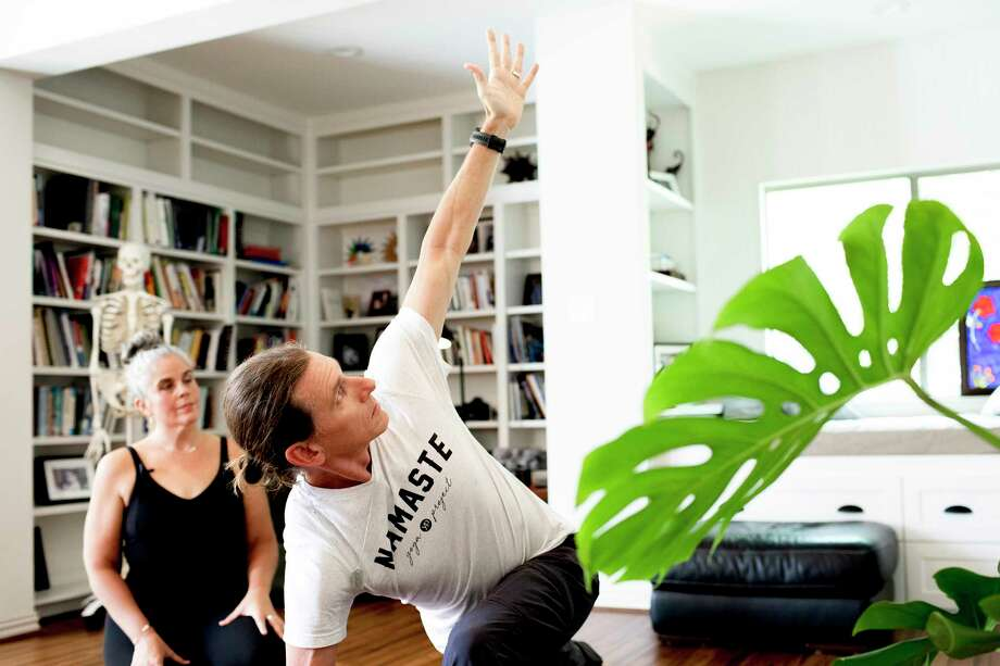 Stacy Dockins instructs her husband, Dave Dockins, as they practice for an online yoga class at their home in Midlothian, Texas, on Thursday, May 7, 2020. Photo: Photo For The Washington Post By Abbi O'Leary / Abbi O'Leary