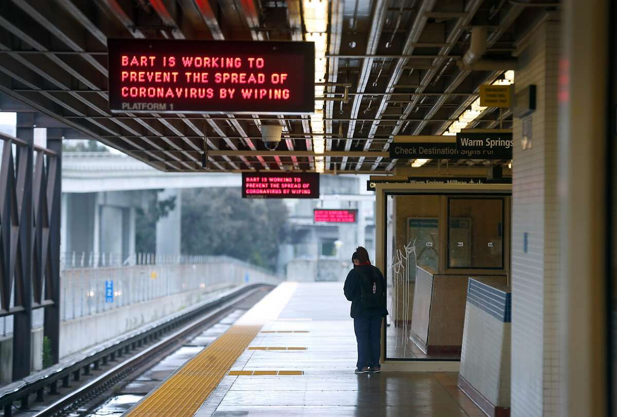 A commuter waits for a train to arrive at the MacArthur BART station in Oakland, Calif. on Tuesday, May 12, 2020. BART is joining transit agencies from around the country in seeking economic federal relief funds because of dwindling ridership during the coronavirus shutdown.