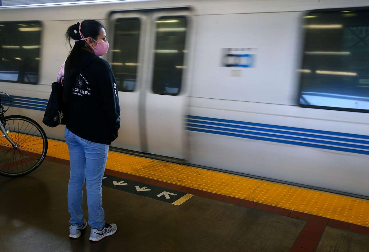 A commuter waits to board a train arriving at the MacArthur BART station in Oakland, Calif. on Tuesday, May 12, 2020. BART is joining transit agencies from around the country in seeking economic federal relief funds because of dwindling ridership during the coronavirus shutdown.