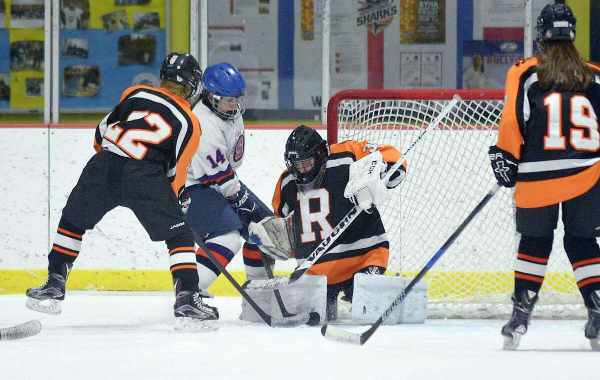 Ridgefield-Danbury goalie Kendal Mountain defends her goal as Stamford-Westhill-Staples skater Stephanie Walsh battles for the puck with Ridgfield's Ally Caiola in a FCIAC girls ice hockey game at Terry Connors Ice Rink in Stamford, Conn. on Wednesday, Jan. 24, 2018.