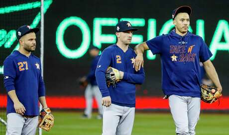 In their proposal for an 82-game season in 2020, MLB owners want players such as Astros second baseman Jose Altuve, from left, third baseman Alex Bregman and outfielder George Springer to accept a salary system that incorporates revenue sharing.
