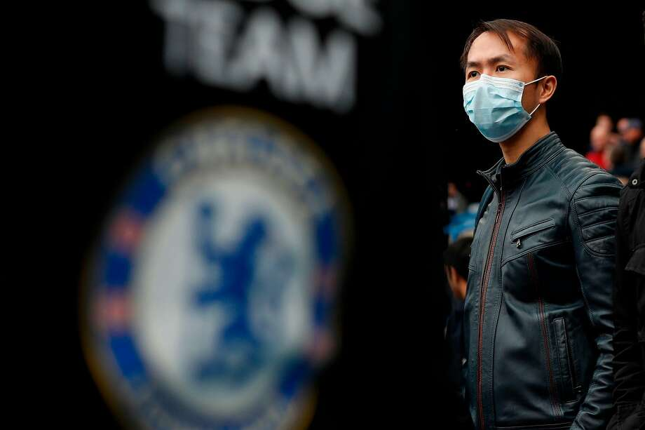 A Chelsea supporter attended an English Premier League game in March wearing a face mask as a precaution against COVID-19. Soon afterward, the league suspended its season. Photo: Adrian Dennis / AFP Via Getty Images