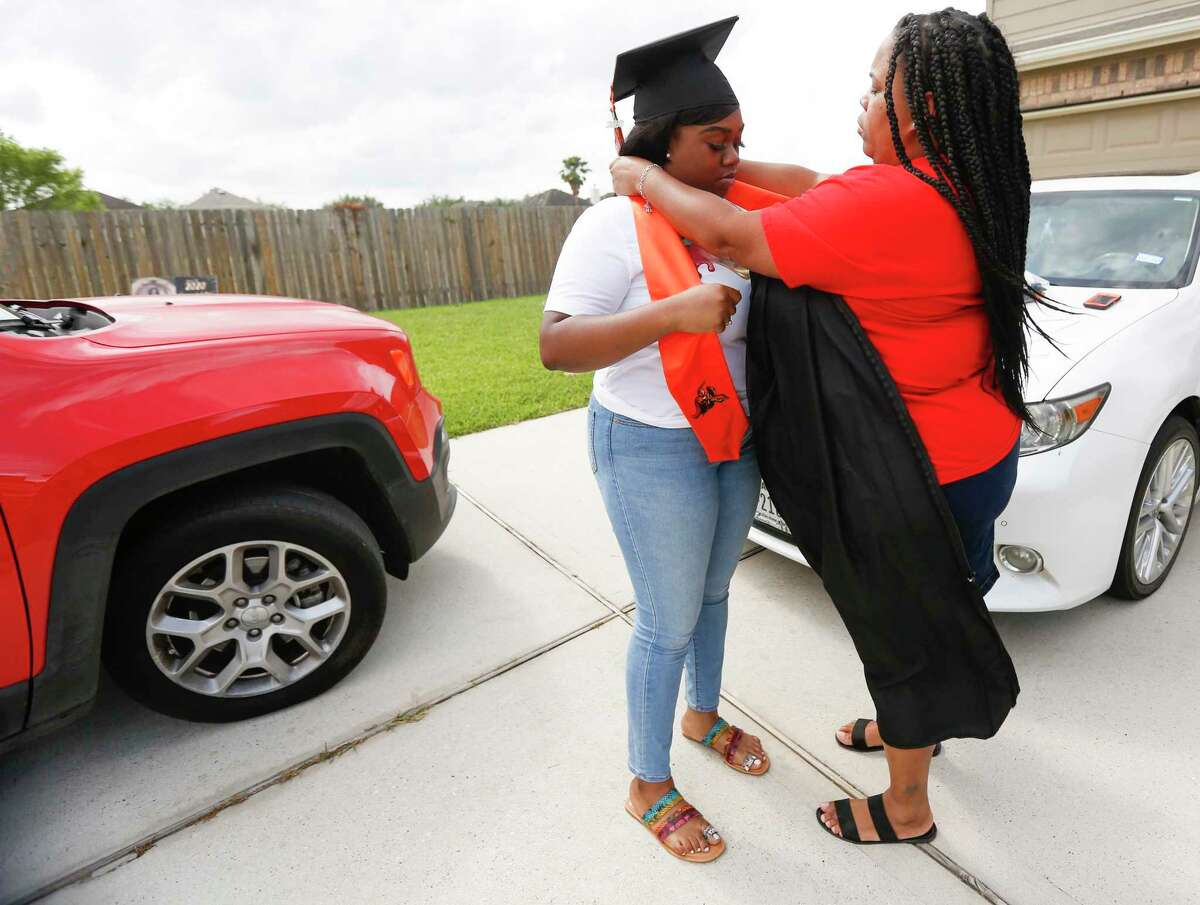 Anaiya Jackson, a senior at Scarborough High School, gets some help from her mom, Robbin Marlin, as she puts on her graduation gown in Houston on Tuesday, May 12, 2020.