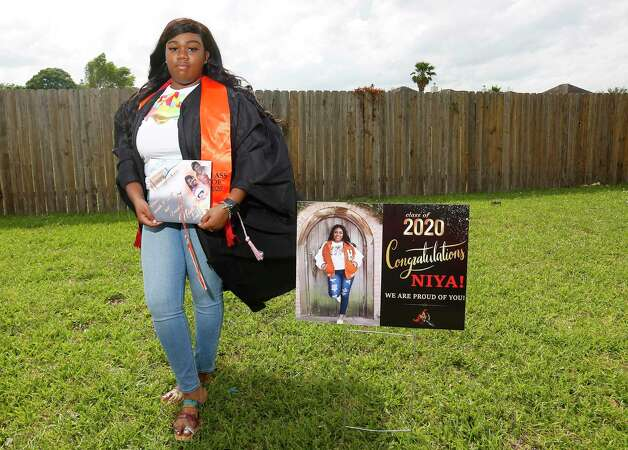 Anaiya Jackson, a senior at Scarborough High School, wears her graduation gown and holds the cap she dedicated to her grandmother who passed away in January in front of her Houston home on Tuesday, May 12, 2020. Photo: Elizabeth Conley, Houston Chronicle / Staff Photographer / © 2020 Houston Chronicle