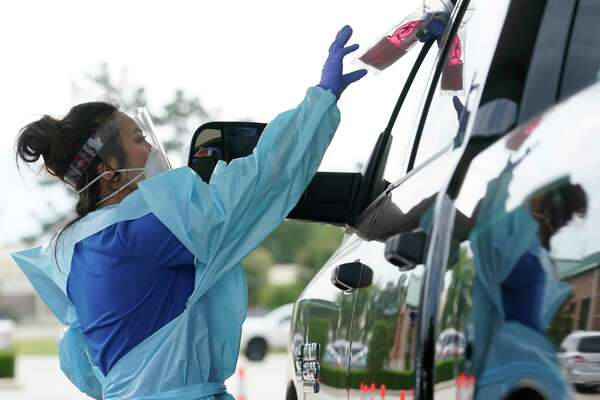 Michelle Nguyen, a Kroger pharmacist, takes a self testing kit from a driver at the COVID-19 testing site held at Montgomery County Precinct 2 Commissioner, 19110 Unity Park Drive, Tuesday, May 12, 2020, in Magnolia. This location of the free Kroger Health free COVID-19 drive through testing is open from 9am to 4pm and will continue through Thursday, May 14.