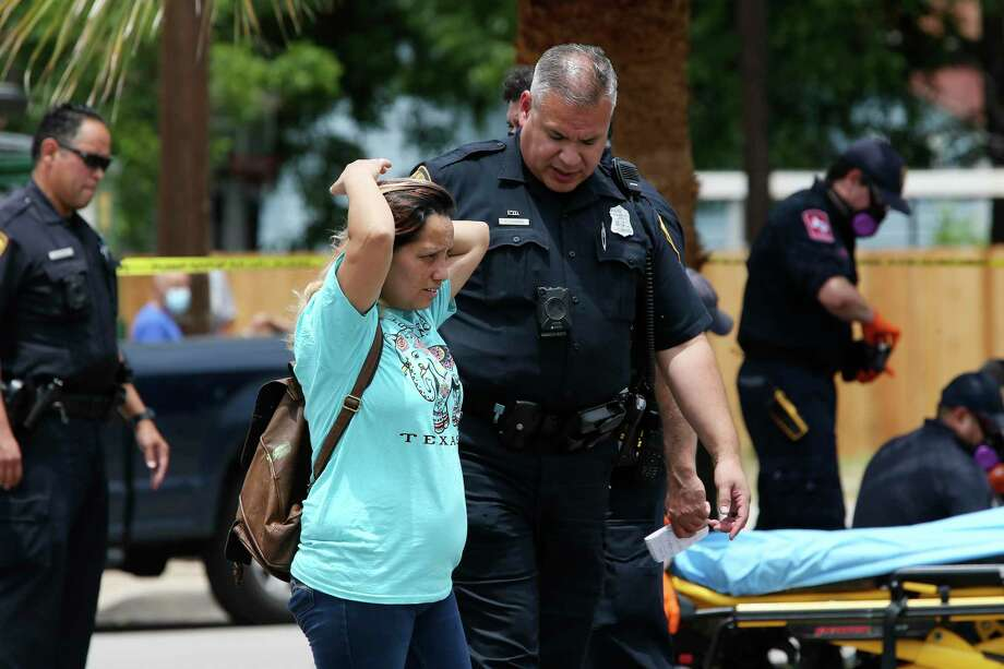 A San Antonio Police officer talks with a woman at the scene of a shooting on the 1800 block of West Commerce Street, Tuesday, May 12, 2020. According to SAPD, the shooting victim, a male, was transported to a local hospital and later pronounced dead. Photo: Jerry Lara, Staff / San Antonio Express-News / **MANDATORY CREDIT FOR PHOTOG AND SAN ANTONIO EXPRESS-NEWS/NO SALES/MAGS OUT/TV   © 2019 San Antonio Express-News