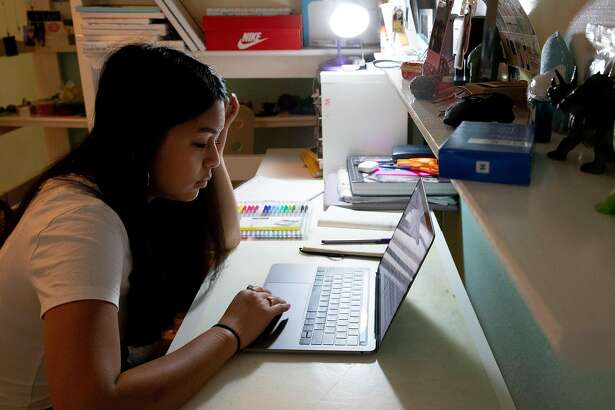 Ligaya Chinn studies for her AP Biology test in her bedroom at her home in Oakland, Calif. Thursday, May 7, 2020. For the first time, high school AP tests will be administered online only in a take-home setting due to the Coronavirus pandemic and shelter-in-place order.