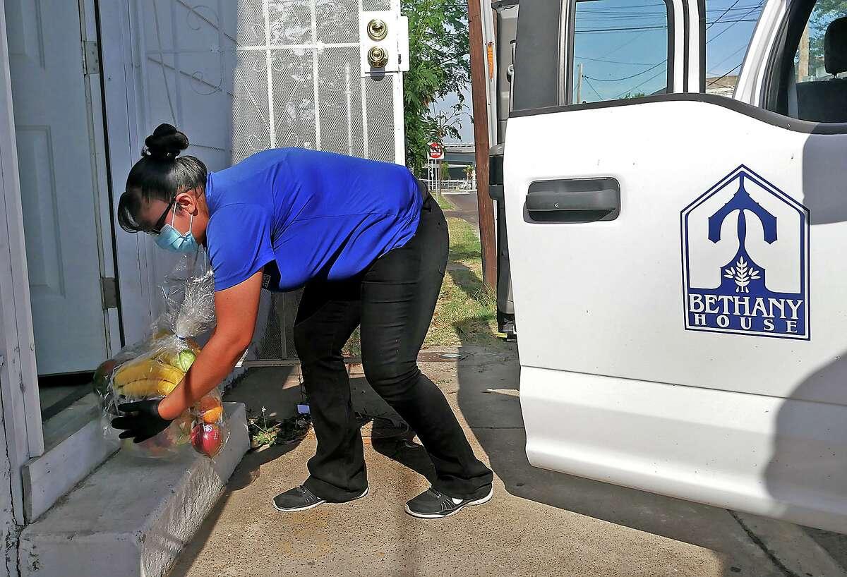 La empleada de Bethany House, Alma Orfila, entrega una de las 200 canastas de frutas, el viernes 8 de mayo de 2020, en la entrada de casas de ancianos y personas enfermas que están confinados en sus hogares y que ya reciben comidas preparadas de Bethany House. Las entregas son parte de los esfuerzos de respuesta por COVID-19 de Betthany House y un donativo monetario de H-E-B.