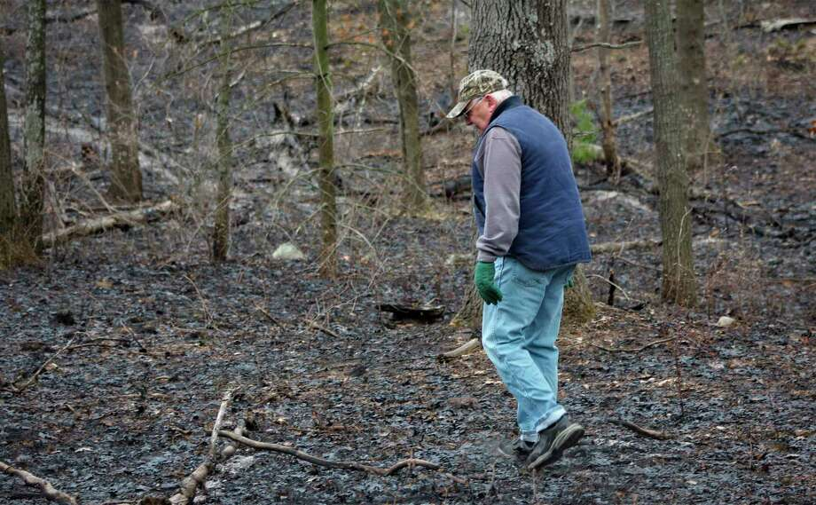 Nearby resident, Dan, walks in what is left of the 10-acres that burnt in Port Crescent State Park last Thursday. (Sara Eisinger/ Huron Daily Tribune)