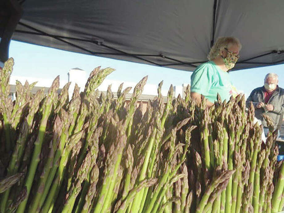A vendor wears a face mask while overseeing a booth selling asparagus at the Jacksonville Farmers Market at Lincoln Square. The market is following its usual summer schedule, but with new social-distancing restrictions amid the COVID-19 pandemic. Photo: Photo Provided By Jeannie Hemphill