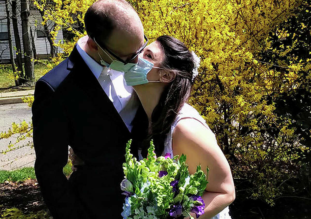 Danielle Cartaxo and Ryan Cignarella kiss while wearing masks after getting married. Barred from getting married in a public space because of lockdown restrictions, Cartaxo and Cignarella were married on the front lawn of the house of a stranger who offered to help.