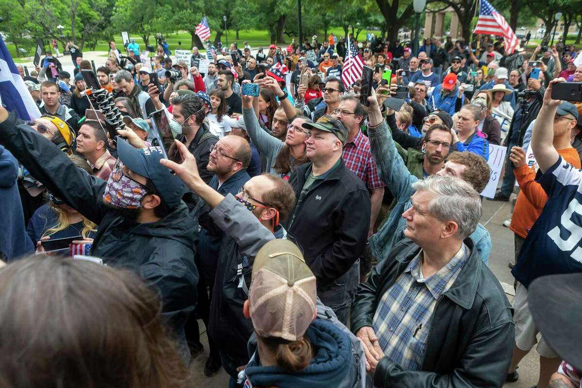 Those in attendance look to get a photo of Alex Jones while gathering at the Texas Capitol in Austin protesting the coronavirus shutdowns, Saturday, April 19, 2020.(Stephen Spillman / for Express-News)