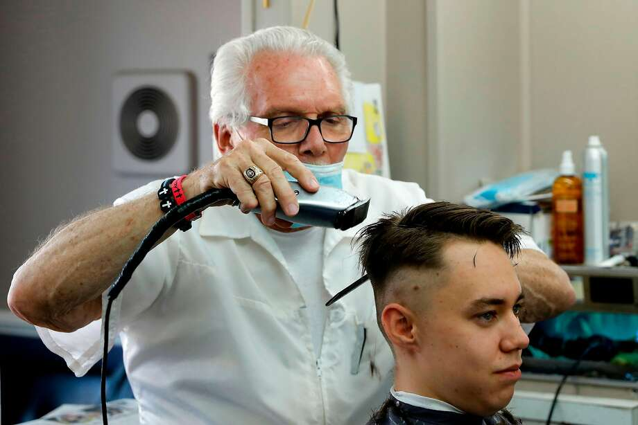 Barber Karl Manke who faces two misdemeanor charges for reopening his shop despite state shutdown orders,  cuts a client's hair at his barber shop on May 12, 2020 in Owosso, Michigan. - The most defiant challenge of Michigan Gov. Gretchen Whitmers pandemic-prompted restrictions on businesses has not come from a titan of industry but from a 77-year-old barber and occasional novelist in a small town between Lansing and Flint. (Photo by JEFF KOWALSKY / AFP) (Photo by JEFF KOWALSKY/AFP via Getty Images) Photo: Jeff Kowalsky, AFP Via Getty Images