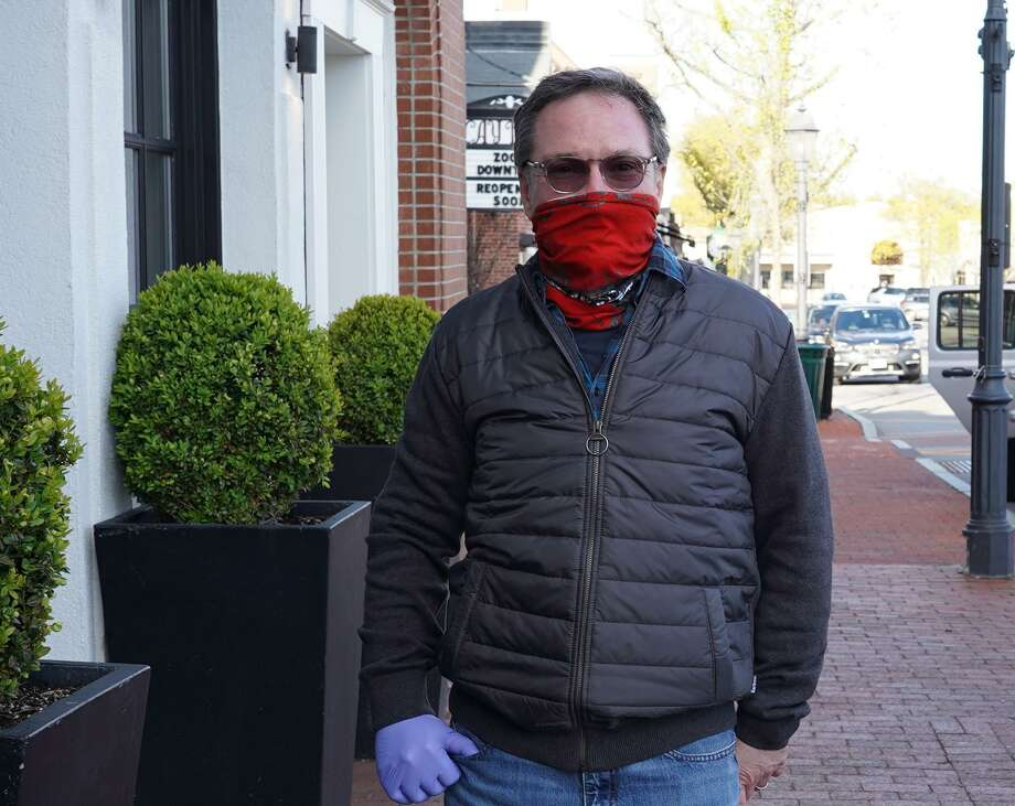 Brian Posner wears a mask on Elm Street in New Canaan recently, in keeping with New Canaan First Selectman Kevin Moynihan's current request for people to wear face coverings, or masks in the town, and State of Connecticut Gov. Ned Lamont's executive order to wear face masks, or cloth face coverings when coming within six feet of another person. They will be required in the town's downtown area come Wednesday, May 20, as the town re-opens amid the coronavirus pandemic. Photo: Grace Duffield / Hearst Connecticut Media