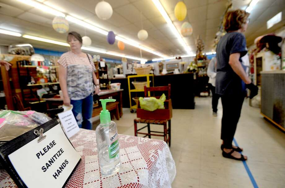 Customers observe distance markers placed on the floor near the check-out counter at The Antique Mall in Lumberton on its first day of reopening Tuesday. Owner Judy Carter, who also owns Country Lane Antique Mall in Lumberton, said though they were allowed to reopen May 1, she decided to wait an extra week to prepare the shops with plenty of sanitizer, new vendor displays, and signage and markers placed throughout the expansive shops to remind customers of social distance protocols. Photo taken Tuesday, May 12, 2020 Kim Brent/The Enterprise Photo: Kim Brent/The Enterprise