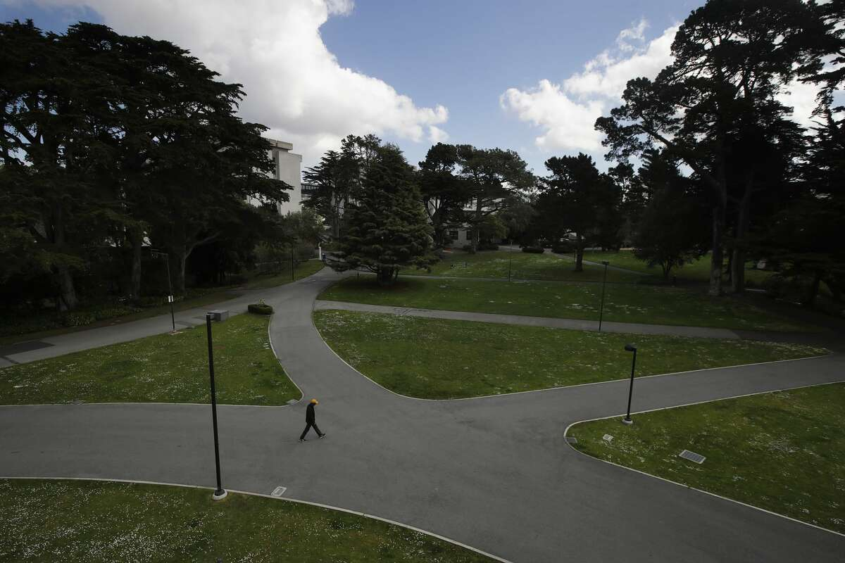 A man walks alone on a path on the San Francisco State University campus in San Francisco, Thursday, March 19, 2020. Cal State Universities will stay closed through the fall semester.