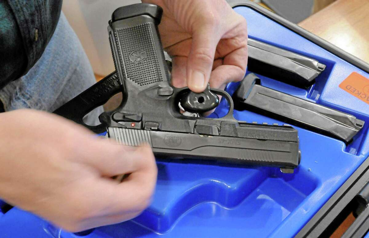 At the TGS Outdoors shop in Branford, Conn., co-owner Brian Owens places a trigger lock on an FNX-45 as part of the sale process. No gun TGS sells leaves the store without a trigger lock placed on it. (Mara Lavitt/New Haven Register) ¬ ¬4/4/13