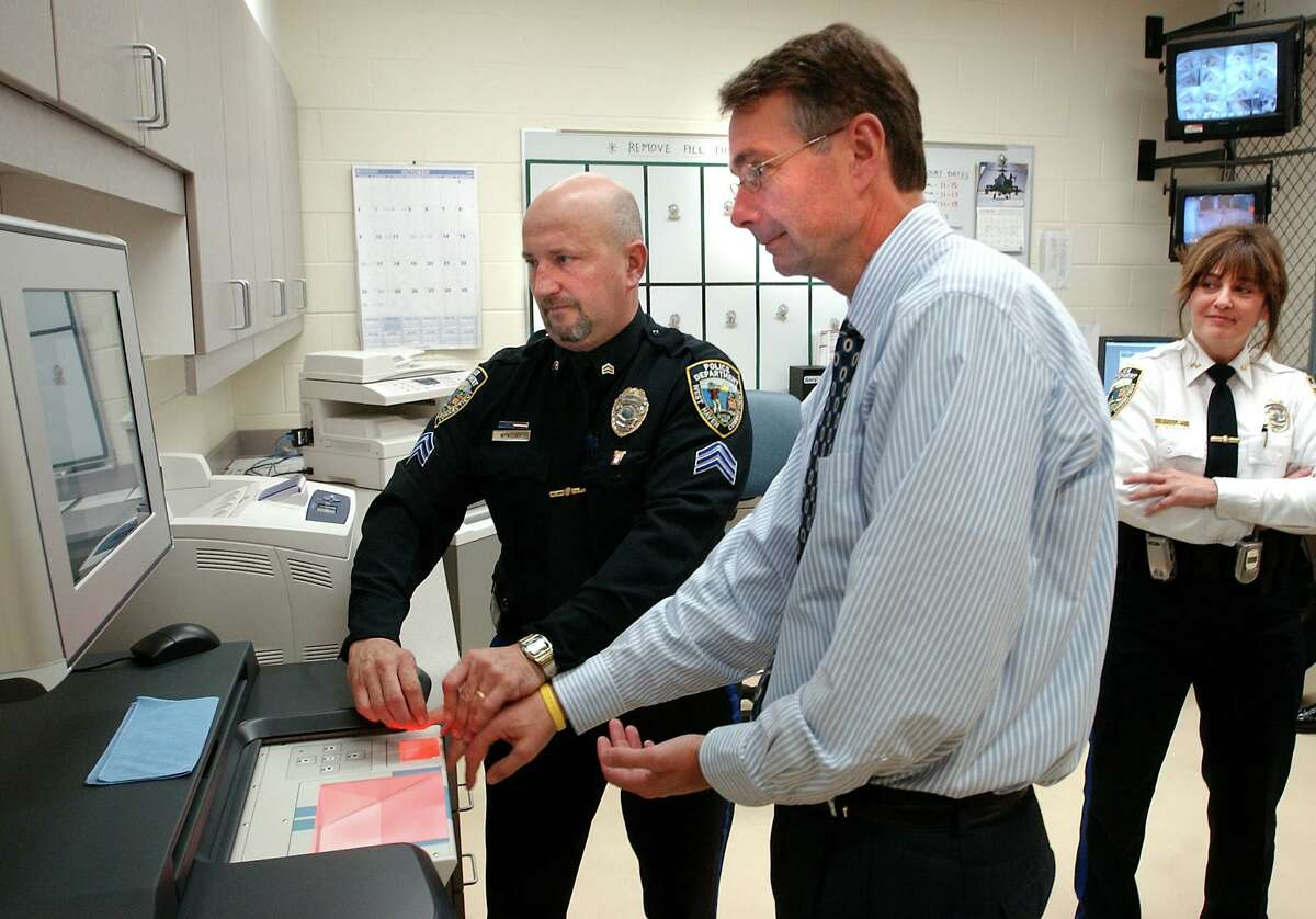WH10/31/05 Fingerprint ML0221B West Haven Mayor H. Richard Borer has his fingerprints taken by Sgt. Joseph Wynosky to demonstrtate the new AFIS LifeScan fingerprinting system at the West Haven Police Dept. West Haven Dept. Police Chief Colleen Smullen is at right. Photo by Mara Lavitt