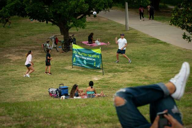 People use a sign urging people to practice social distancing as a net to play volleyball along Buffalo Bayou near Eleanor Tinsley Park, Tuesday, May 12, 2020, near downtown Houston. Photo: Mark Mulligan, Staff Photographer / © 2020 Mark Mulligan / Houston Chronicle