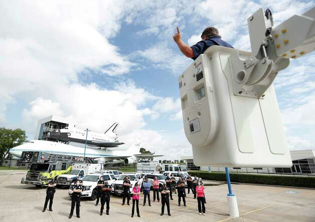 """Bryan Anderson, directs a group shot of the Nassau Bay, Webster, and Johnson Space Center first responders from a bucket truck for his personal project, """"First Responders Texas Strong"""" at Space Center Houston, in Houston, Wednesday, May 13, 2020.  Anderson, a local wedding photographer, has been photographing multiple first responder departments around the Houston area, shooting dramatic socially distanced group shots for a project he calls """"First Responders Texas Strong"""". """"First responders and medical teams need to be reminded we support them, ad they have each other's back."""" Photo: Karen Warren, Staff Photographer / © 2020 Houston Chronicle"""