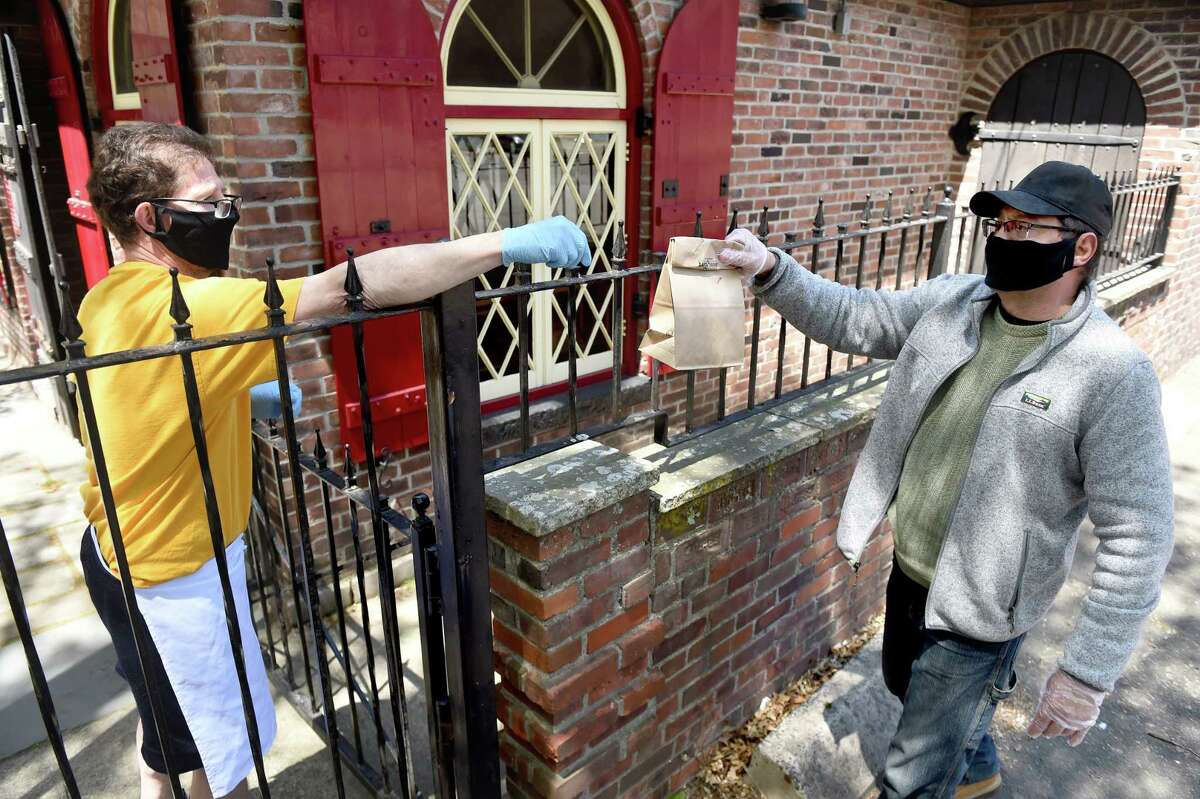 Fourth generation owner of Louis' Lunch Jeff Lassen hands parking lot attendant and regular customer Rey Colon his lunch over a fence next to the hamburger joint in New Haven on May 13, 2020.