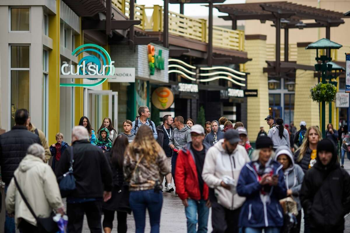 People walk in Downtown Disney, making their way toward the entrance to Disneyland on March 13, 2020 in Anaheim, Calif. Disney's two Southern California theme parks, California Adventure and Disneyland, have been shut down temporarily as a result of the spread of the coronavirus.