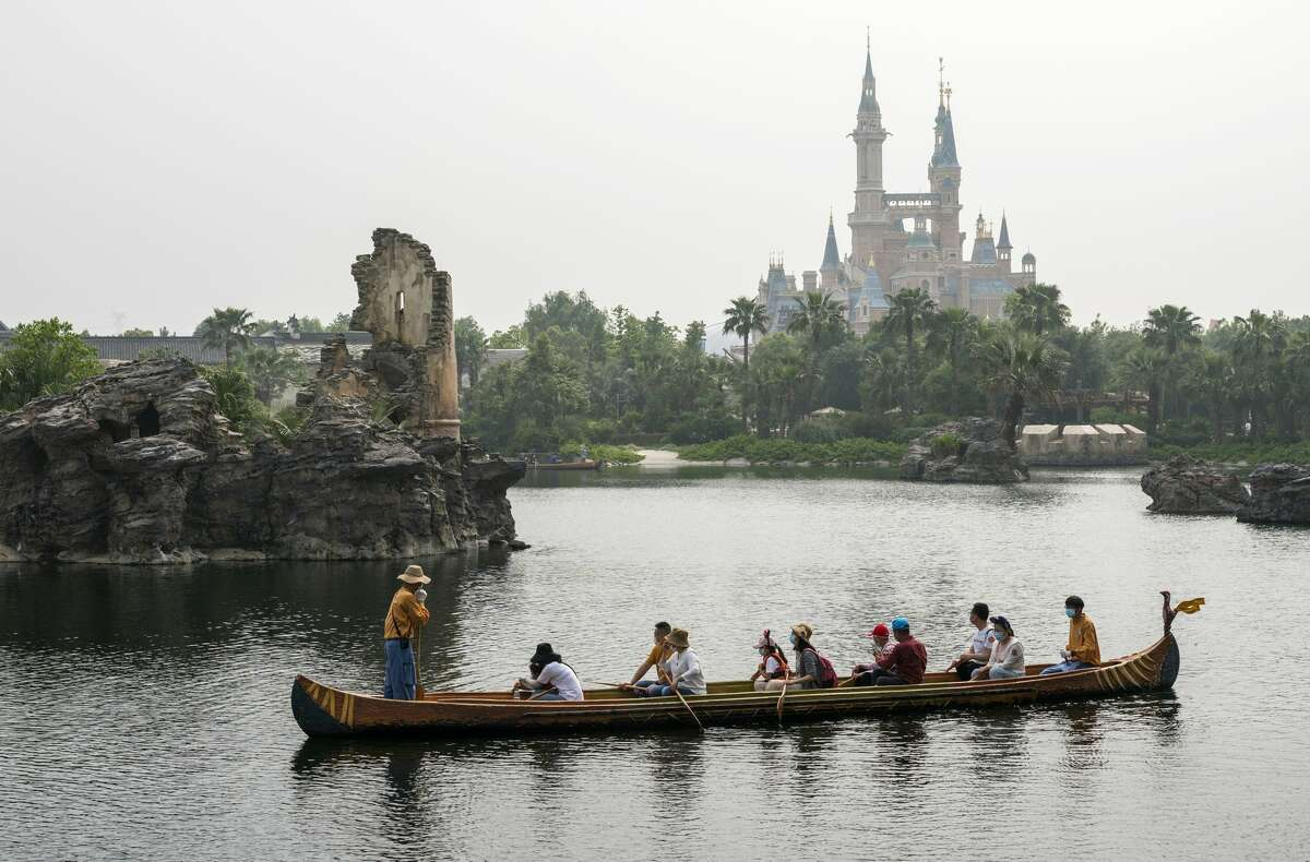 Despite the ubiquity of face masks and some social-distancing measures, photos from the reopening on May 11 looked largely familiar to fans of the parks. Guests canoed, snapped selfies and took a spin on Dumbo the Flying Elephant. They even held parades and took in shows - with noticeably more distance between families than a usually jam-packed Disneyland parade route.