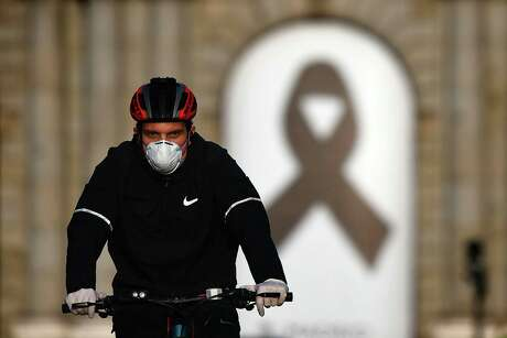A cyclist wearing a face mask rides his bike in front the Puerta de Alcala in Madrid on May 9, 2020, during the hours allowed by the government to exercise, amid the national lockdown to prevent the spread of the COVID-19 disease. - Spain's two biggest cities Madrid and Barcelona will not enter the next phase out of coronavirus lockdown along with many other regions next week, the government said. (Photo by Gabriel BOUYS / AFP) (Photo by GABRIEL BOUYS/AFP via Getty Images)