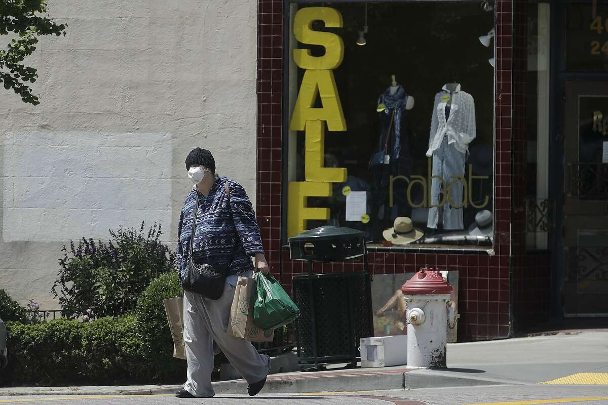 A woman wears a face mask while carrying shopping bags during the coronavirus outbreak in San Francisco, Thursday, May 7, 2020. California Gov. Gavin Newsom is preparing to loosen the state's stay-at-home order to allow some businesses to reopen as early as Friday. Newsom is scheduled to reveal new guidelines Thursday that could allow reopening of some retail outlets, including clothing shops, bookstores and florists, but they must heed social distancing rules. (AP Photo/Jeff Chiu)