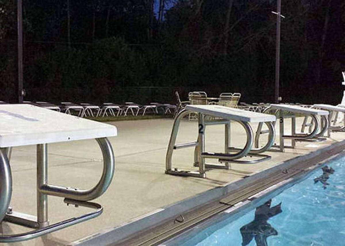 The starting blocks sit lonely at a pool.