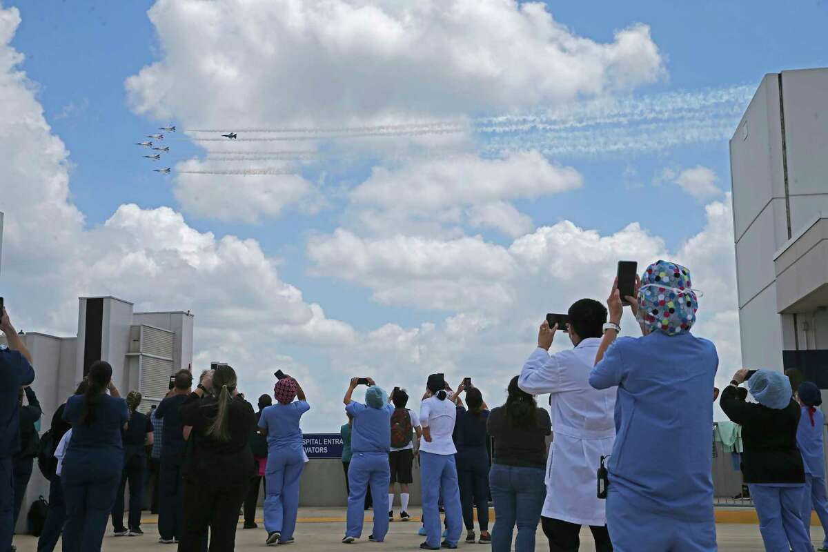 The Thunderbirds fly over the Medical Center area as staff and family members watch from a top of a garage at Methodist Hospital, Wednesday, May 13, 2020.