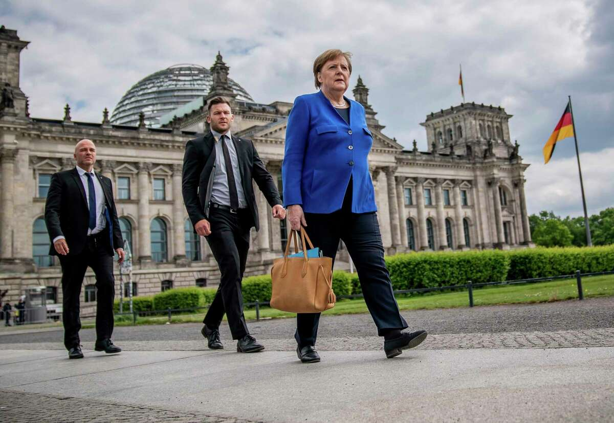 Chancellor Angela Merkel walks to the Chancellery on foot, accompanied by her bodyguards, after the government questioning in the Bundestag in Berlin, Germany, Wednesday, May 13.