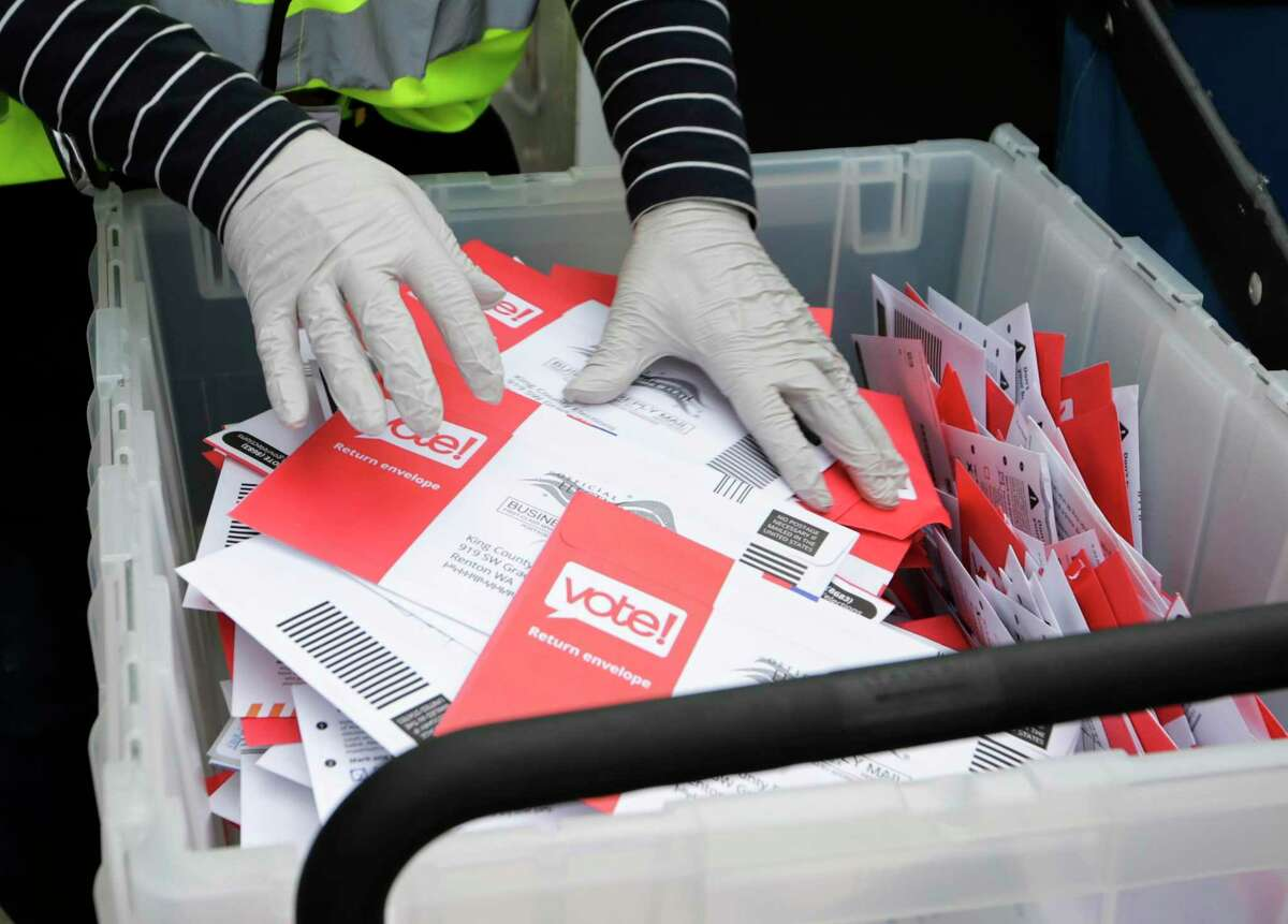 A worker in the state of Washington handles mail-in votes. The novel coronavirus has led to a push for expanded mail-in voting in Texas, but Attorney General Ken Paxton has argued this will open the door to fraud and violates the state's election law.