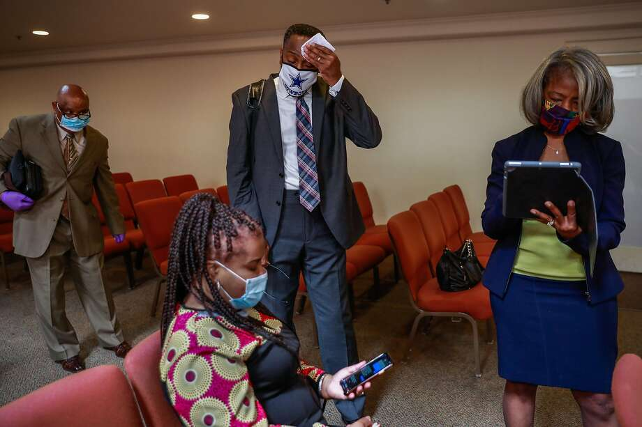 Pastor Kenneth Reece (center) wipes his forehead as his wife Lisa Reece (second from left) looks at her phone moments after their virtual church service at Cornerstone Missionary Church in the Bayview district on Sunday, May 10, 2020 in San Francisco, California. One of the congregants, Tessie Henry, contracted coronavirus from a funeral at the church and later died. Photo: Gabrielle Lurie / The Chronicle
