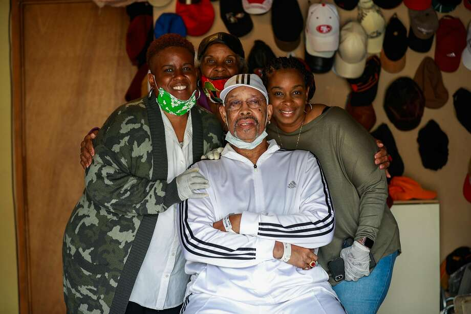 Wilbur Morris, 80, poses for a photograph with his daughters Racquel Gatlin (left) Nichelle Miller� (right) and wife Bessie Morris (center) in their garage on Saturday, May 2, 2020 in the Bayview district of San Francisco, California. Wilbur suffered a very serious case of covid-19 where he was intubated and put into a coma for three weeks. Photo: Gabrielle Lurie / The Chronicle