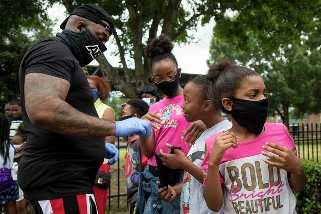 """Rap artist Trae The Truth hands out masks to Kayla Stelly, Serenity Johnson and Kassie Kinds in the Third Ward on Wednesday, May 13, 2020 in Houston. The rapper spent the day handing out 10,000 masks to people in neighborhoods all around the city. """"I am trying to get masks to people who wouldn't normally be able to get one,"""" he said. Photo: Brett Coomer, Staff Photographer / © 2020 Houston Chronicle"""