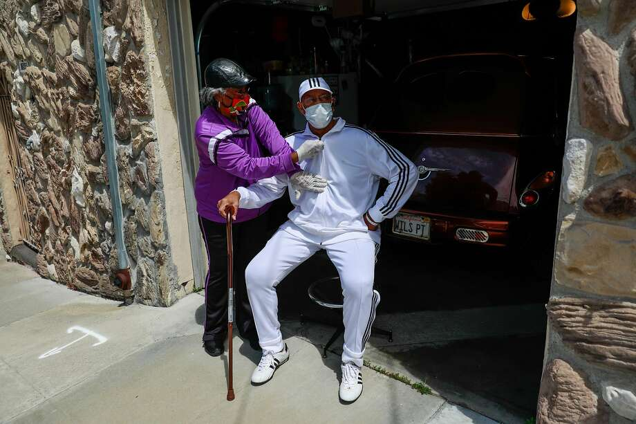 Bessie Morris (left) zips her husband Wilbur Morris�, 80, jacket after getting home from the hospital and rehab following a serious case of covid-19 on Saturday, May 2, 2020 in the Bayview district of San Francisco, California. Photo: Gabrielle Lurie / The Chronicle