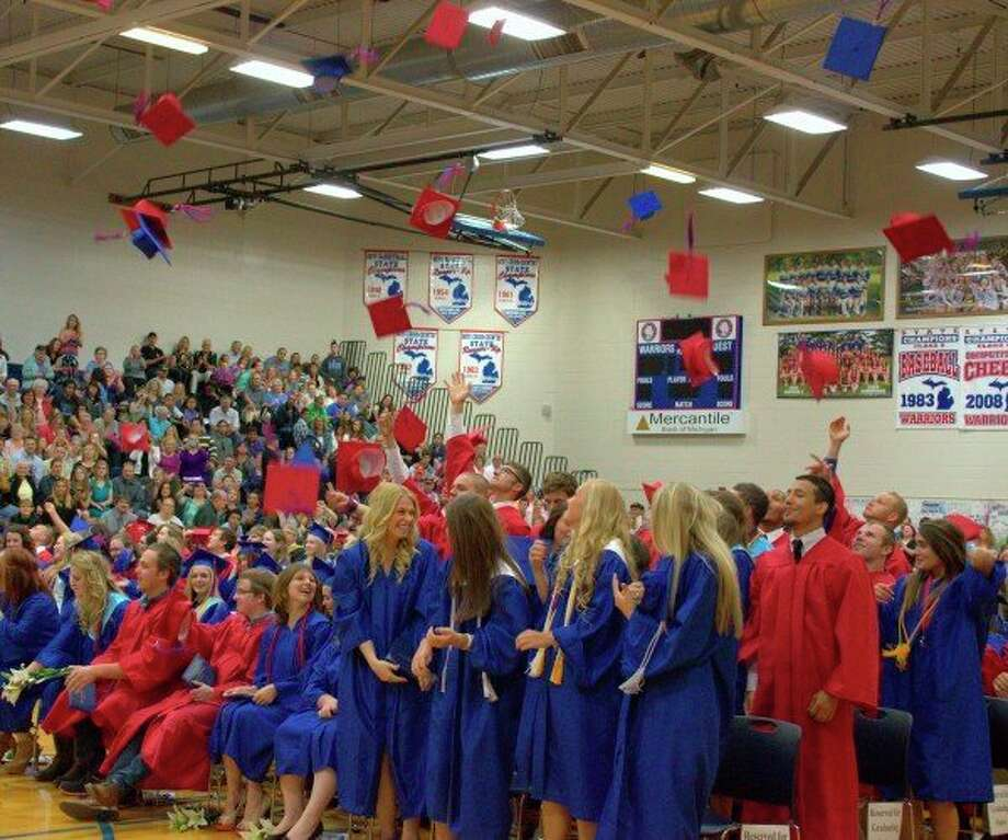 Former Chippewa Hills seniors throw their caps in the air at a previous graduation ceremony. This year, graduation will take place at the high school parking lot. (Pioneer file photo)