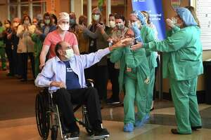 Retired surgeon John Famiglietti, 71, of Brookfield, is cheered by Danbury Hospital staff as he is Wednesday after winning a seven-week battle with COVID-19.