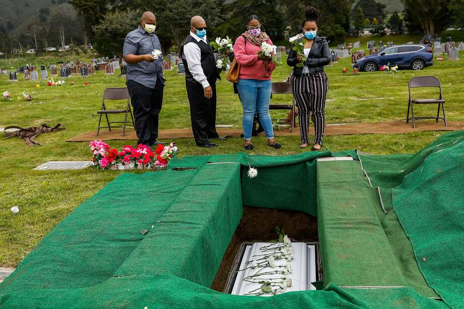 (L-r) Lothell Holloway, Robert Henry, Raneisha Henry and Rashwan Henry at the burial of their grandmother and mother Tessie Henry who died of Covid-19 at the age of 83 is buried on Wednesday, April 8, 2020 in Colma, California. Photo: Gabrielle Lurie / The Chronicle