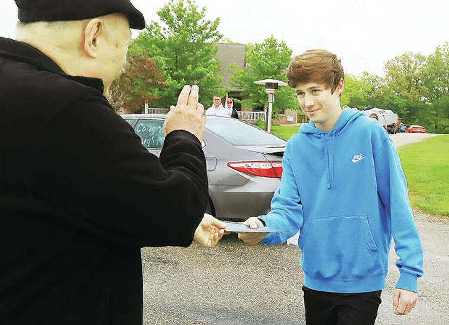 """Father Tom Liebler blesses Ryan DeClue as he hands him his diploma from Our Lady Queen of Peace school in Bethalto as family and friends braved chilly temperatures to watch a brief """"drive-by"""" graduation ceremony in front of DeClue's home. The school honored its 11 eighth grade graduates with a caravan Wednesday,"""