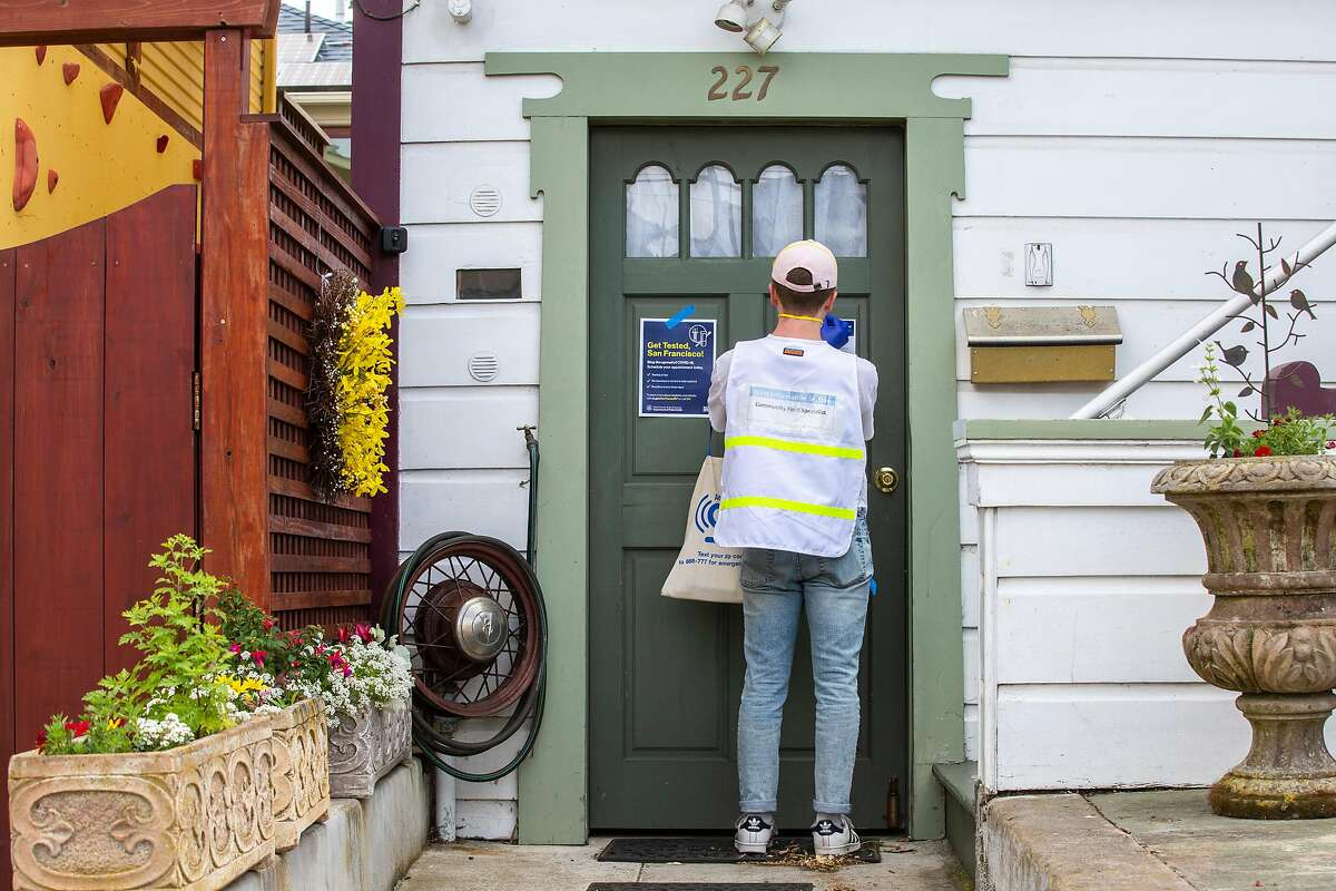 Vincent Page, 23, goes door-to-door in the Excelsior neighborhood to post health leaflets, Tuesday, May 12, 2020, in San Francisco, Calif. The leaflets contained appointment information for CityTestSF, which provides free COVID-19 testing for essential workers and adults living in San Francisco.