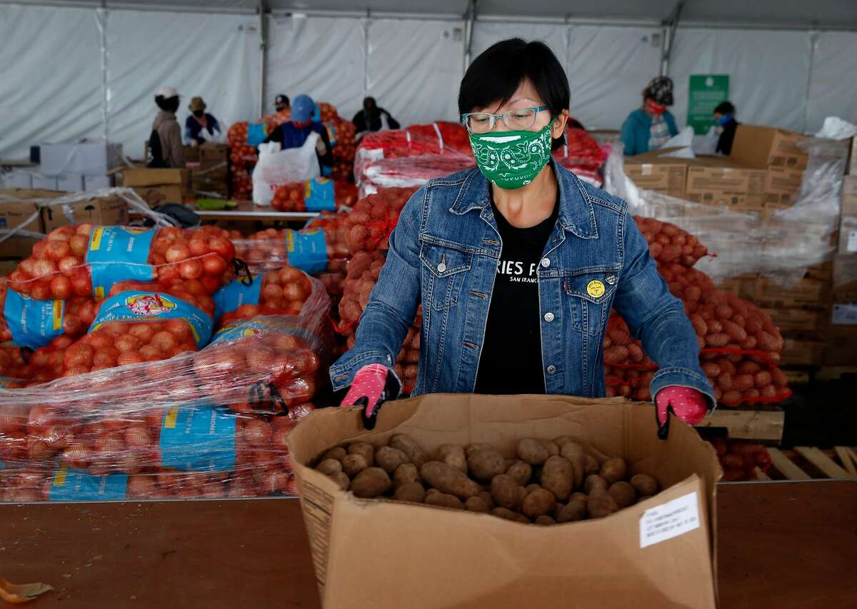 Jen Woo, a librarian from the West Portal branch, sorts potatoes on her volunteer shift at the SF-Marin Food Bank during the coronavirus pandemic in San Francisco, Calif. on Wednesday, May 13, 2020.