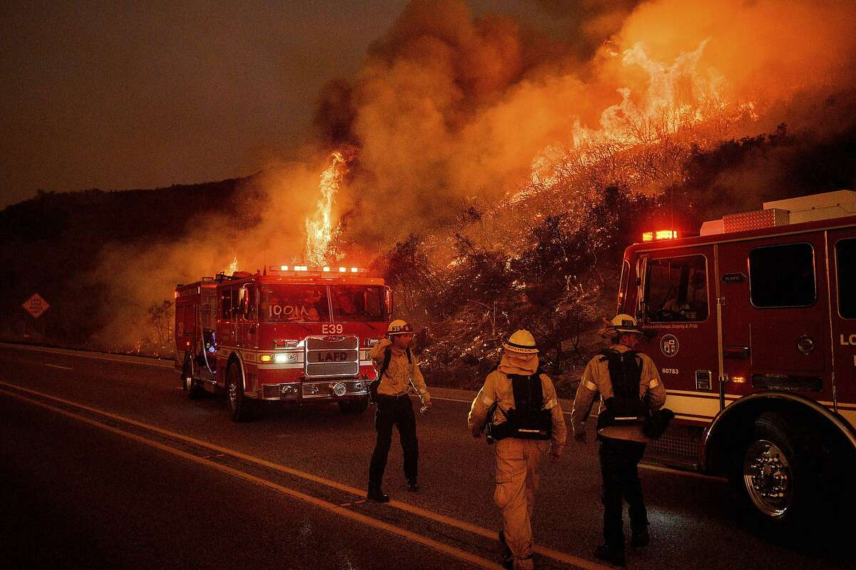 FILE - In this Nov. 26, 2019, file photo, firefighters battle the Cave Fire burn above Santa Barbara, Calif. Fifty years after the first Earth Day helped spur activism over air and water pollution and disappearing plants and animals, significant improvements are undeniable but monumental challenges remain. Minority communities suffer disproportionately from ongoing contamination. Deforestation, habitat loss and overfishing have wreaked havoc on global biodiversity. And the existential threat of climate change looms large. (AP Photo/Noah Berger File)