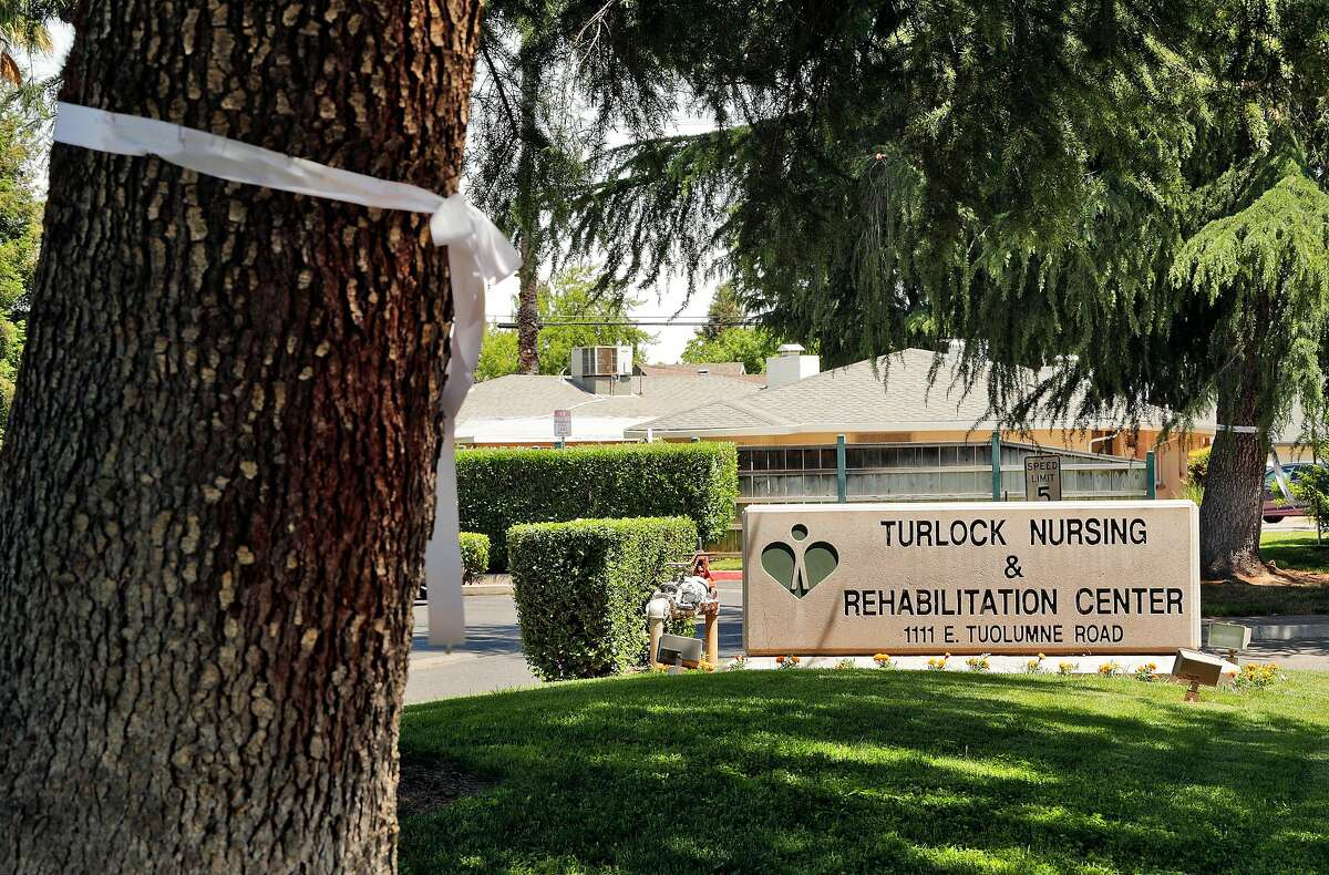 White ribbons are tied around pine trees in front of the Turlock Nursing and Rehabilitation Center where 14 residents have died from COVID-19 in Turlock, Calif., on Wednesday, May 13, 2020. About 150 residents and staff have tested positive at the facility.