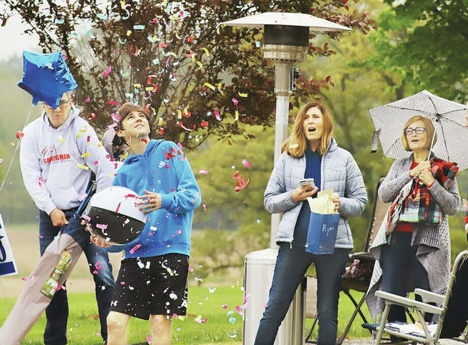 """Ryan DeClue looks up at confetti shot into the air by the staff of Our Lady Queen of Peace school Wednesday during his """"drive-by"""" eighth grade graduation. About a dozen staff members with decorated cars arrived at his homefor a brief graduation ceremony. Other creative plans are being organized by many area high schools. A story about Our Lady Queen of Peace's caravan appears inside."""